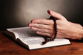 11834959-hands-holding-wooden-rosary-over-open-russian-holy-bible-on-grey-background-w800-h600